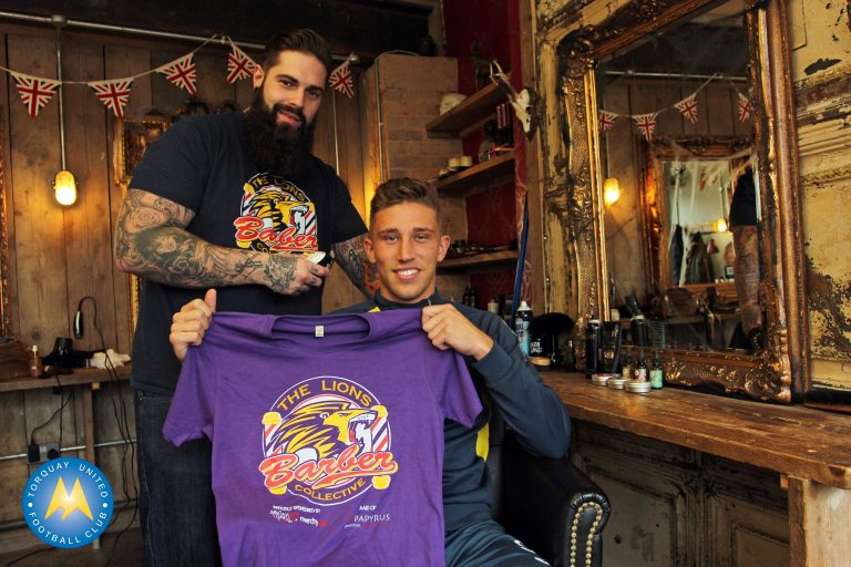 Tom Chapman, founder of The Lion's Barber Collective, with Torquay footballer Angus MacDonald